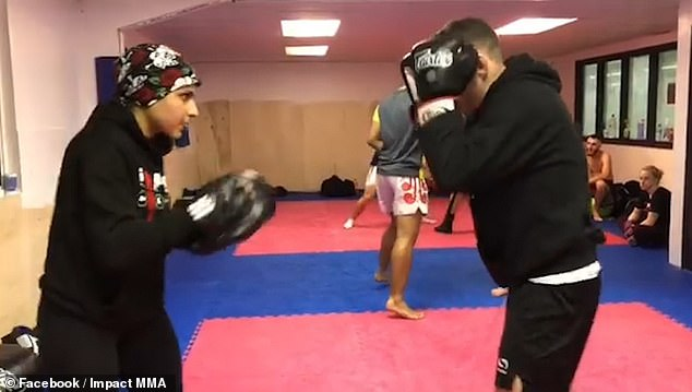 Sai Aletaha pictured holding pads during a training session with a fellow MMA practitioner
