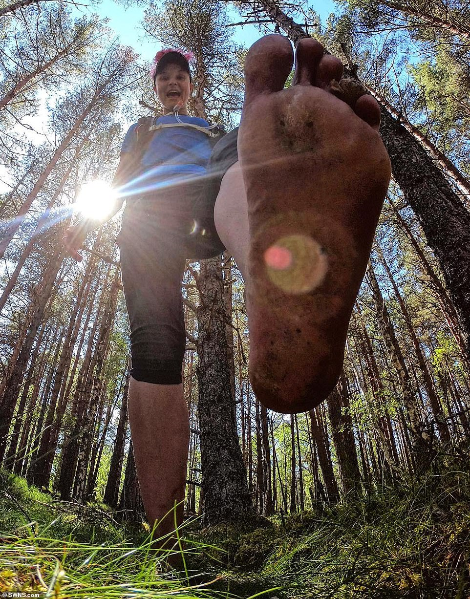 Anna takes a light-hearted picture among the woodland trees in Aviemore, Highlands of Scotland, during the 2,620 trek, and reveals a glimpse of her dirty feet