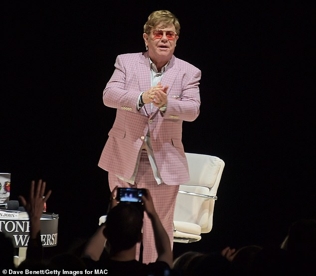 Suave: As ever Elton displayed his eccentric sense of style in a pale pink checked suit and a white shirt as he arrived on the stage to a thunderous applause