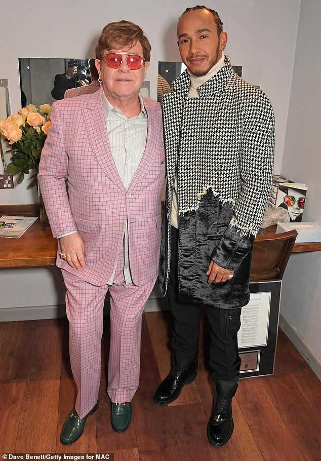 Best friends: He was in high spirits as he posed with Formula One legend Lewis Hamilton at his event