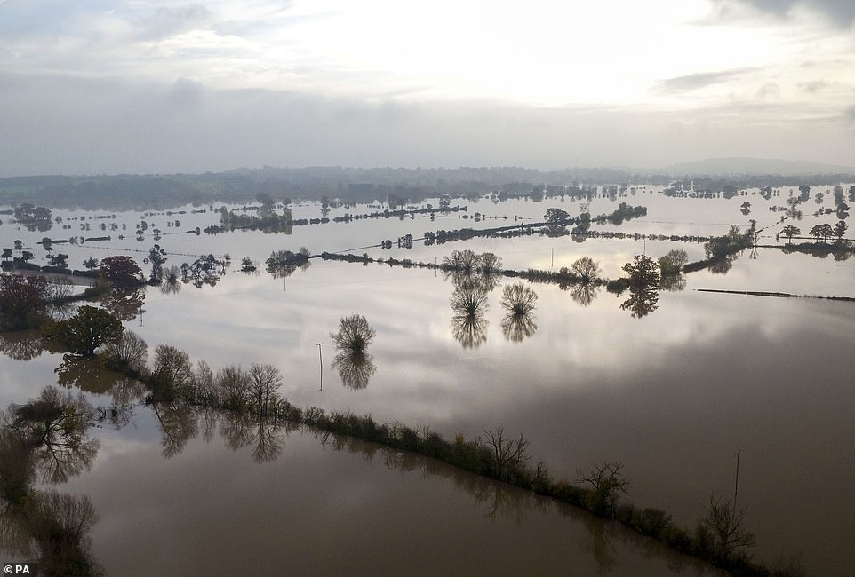 The astonishing landscape of flooded fields near Forthampton in Gloucester today, where sunlight piercing through the morning gloom created an almost unearthly scene