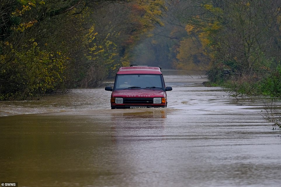 A Land Rover wades through floodwaters near the village of Lower Apperley in Gloucestershire after the River Severn flooded theB4213 between Lower Apperley and Tirley