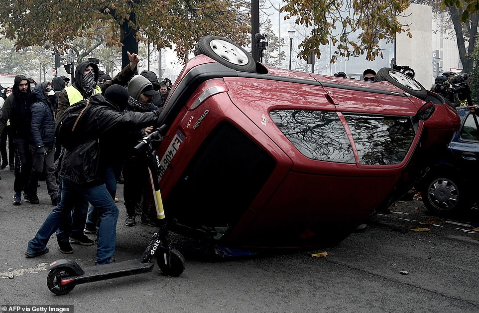 Protesters wearing masks and hoodies turn over a red Citroen in the violent scenes of unrest today which have gripped France for a year