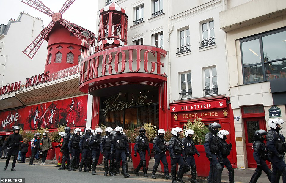 """Police officers walk past Moulin Rouge cabaret as they secure a demonstration to mark the first anniversary of the """"yellow vests"""" movement"""