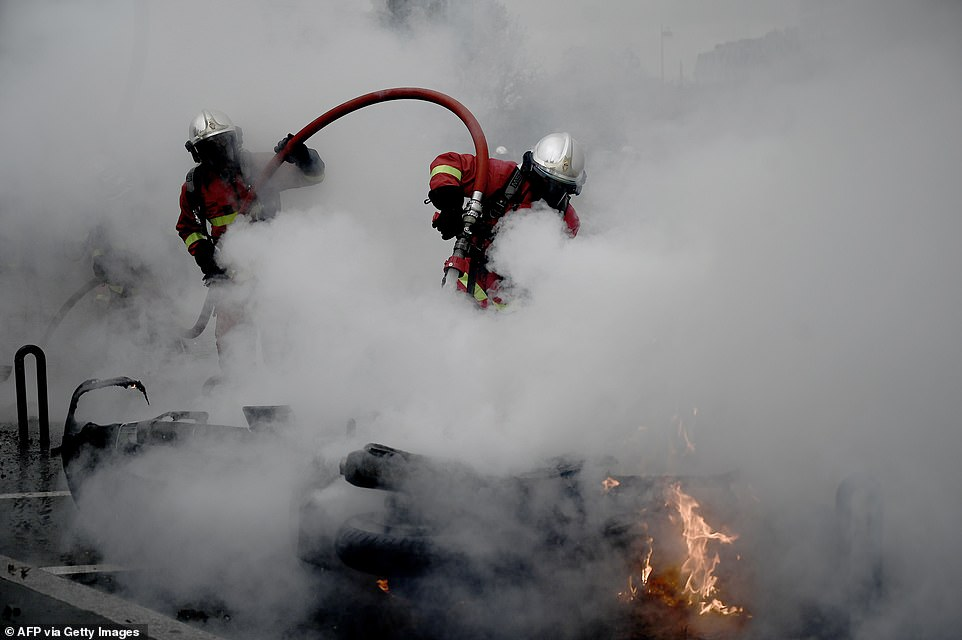 A firefighter tries to extinguish a burning motorcycle near the Place d'Italie in Paris today as violence once again escalated in the capital