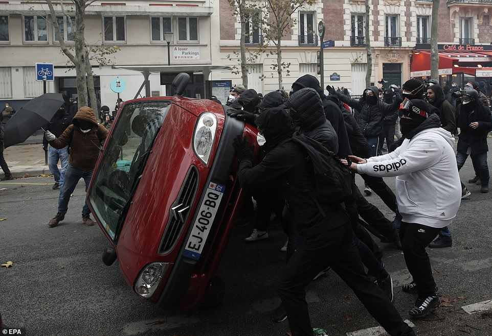 Masked protesters overturn a car as they clash with riot police during the 'Act 53' demonstration, the 53rd consecutive week of unrest