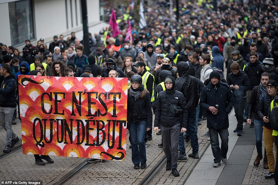 """Protesters hold a banner reading """"It's only the beginning"""" as they attend during a demonstration marking the first anniversary of the """"yellow vest"""" (gilets jaunes) movement"""