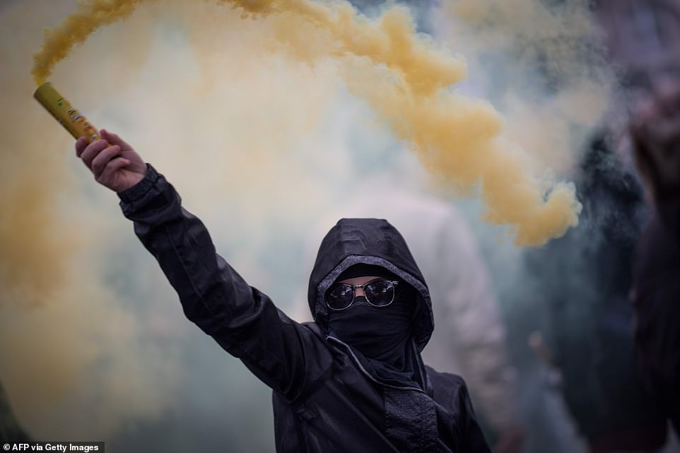 """A protester waves a smoke generator during a demonstration marking the first anniversary of the """"yellow vest"""" (gilets jaunes) movement"""