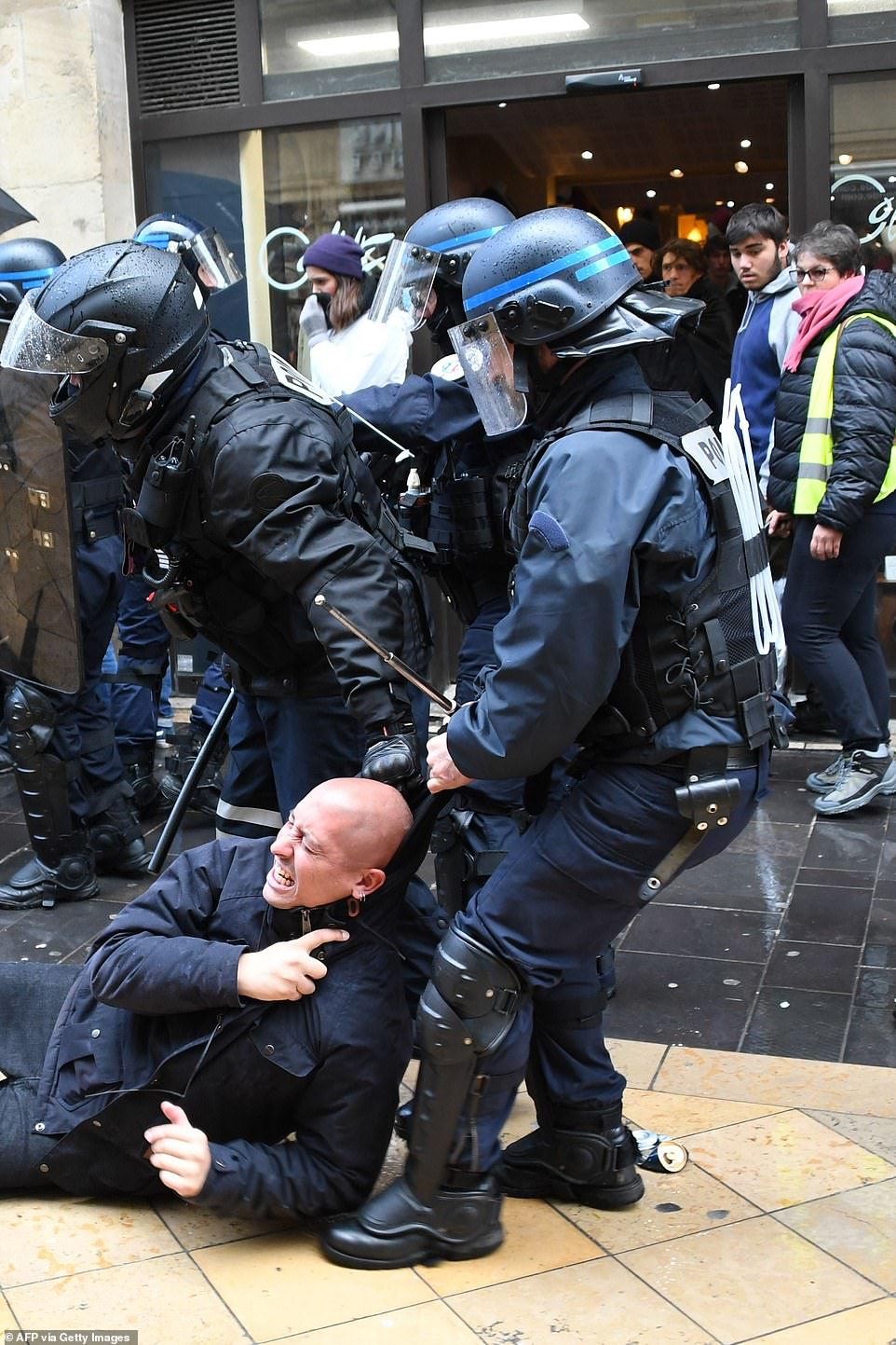 French anti-riot policemen detain a man during the demonstrations that took place in Paris today