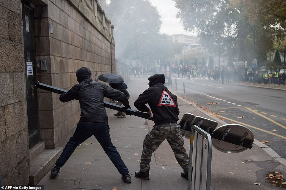 Protesters try to break through the door of the prefecture today using a sign post from the side of the road
