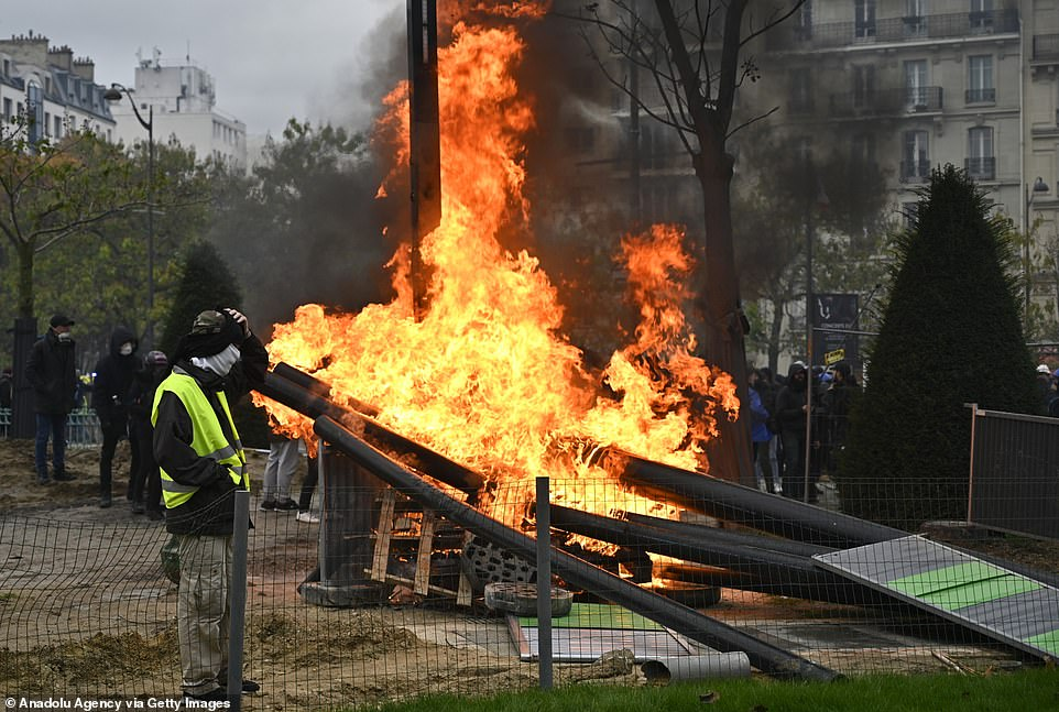 A yellow vest protestor stands near a fire during 'Gilets Jaunes' demonstrations in Paris, France today