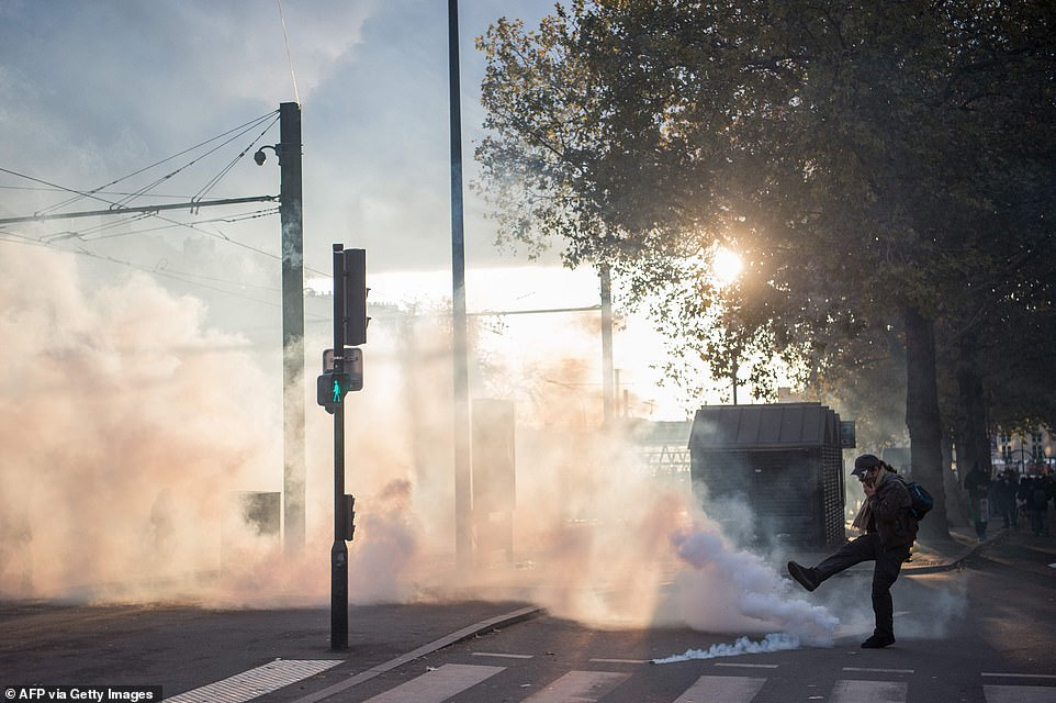 """A man kicks a tear gas canister during a demonstration marking the first anniversary of the """"yellow vest"""" (gilets jaunes) movement"""