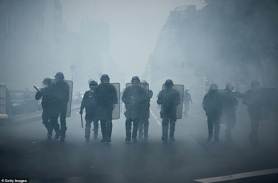Trade unions have called on railway workers, Paris public transport staff, truck drivers and civil servants to strike against a pensions overhaul on December 5. Pictured:French Riot Police charge through clouds of tear gas