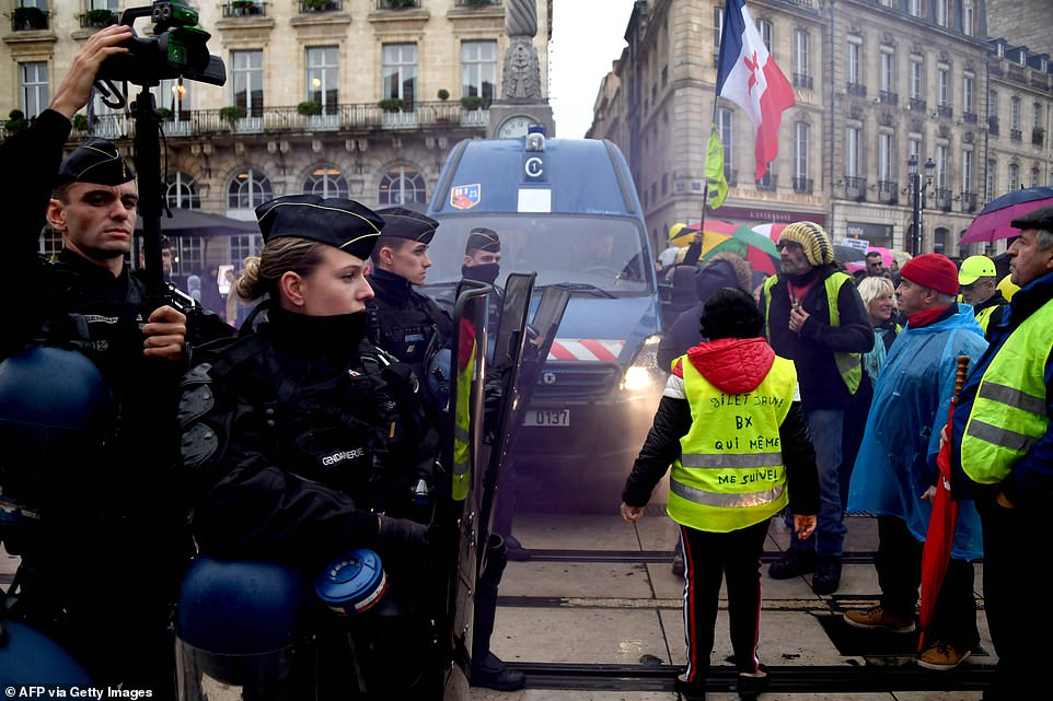"""French anti-riot policemen face protesters during a demonstration marking the first anniversary of the """"yellow vest"""" (gilets jaunes) movement in Bordeaux"""
