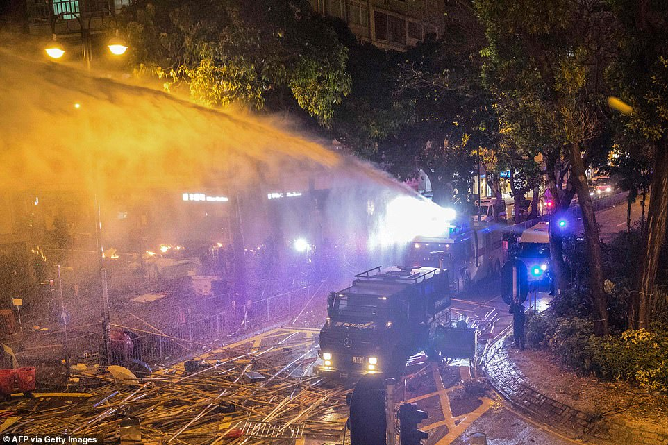 Police deploy a water cannon to disperse protesters attempting to march towards Hong Kong Polytechnic University