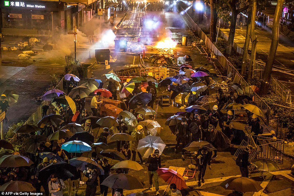 Protesters retreat during clashes with police as they attempt to march towards Hong Kong Polytechnic University in Hung Hom district of Hong Kong