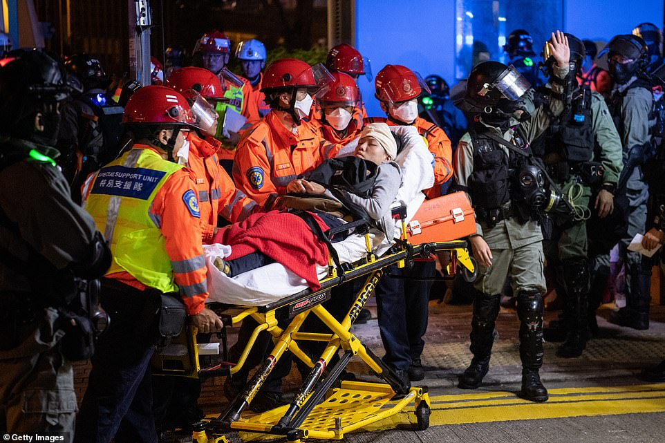 A protester who appears to have been shot in the head by a rubber bullet fired by police is placed on a stretcher and taken away from Hong Kong PolyU, which has been the site of intense clashes