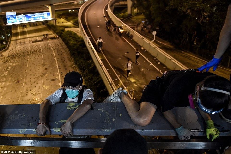 Students trapped on the Hong Kong Polytechnic University campus by police staged a daring escaped by scaling down ropes attached to a bridge and on to a motorway below, before being taken away on bikes