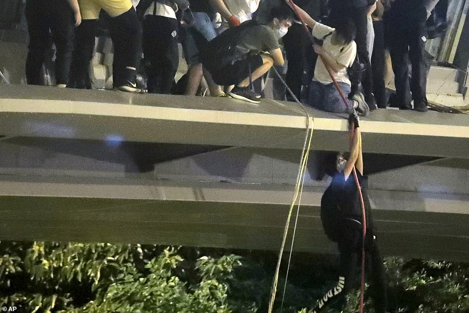 Protestors use a rope to lower themselves from a pedestrian bridge to waiting motorbikes in order to escape from Hong Kong Polytechnic University and the police