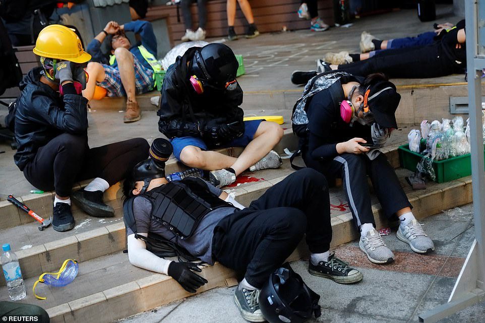 Exhausted demonstrators collapse on the floor inside the university campus after a night of fierce clashes with police