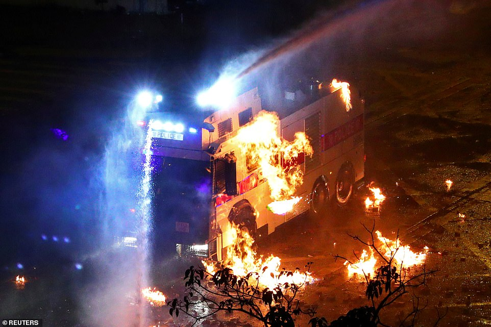 A riot police vehicle is set on fire during clashes outside Hong Kong Polytechnic University in Hong Kong, as police looked to storm the campus