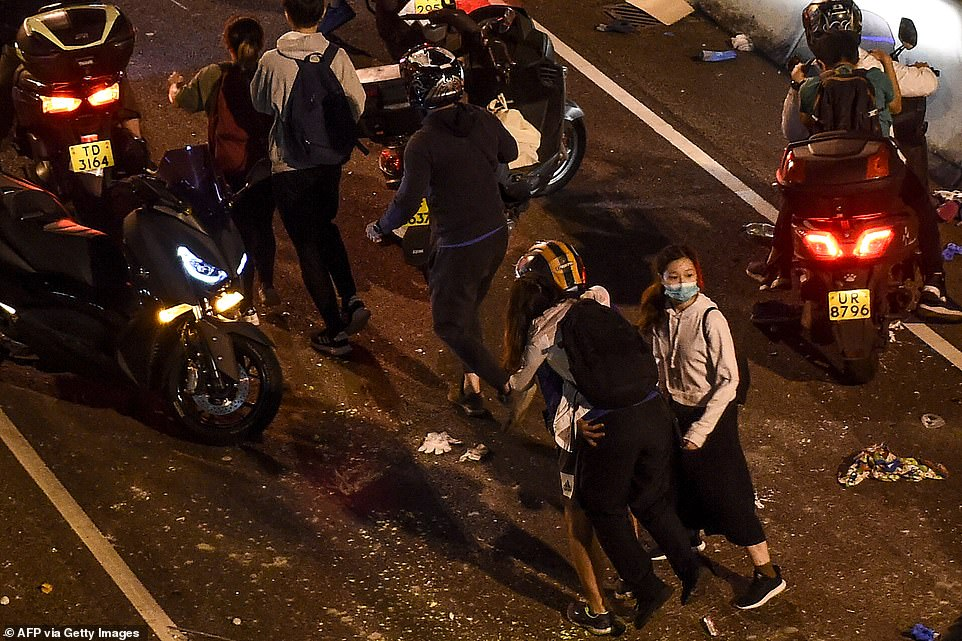 Students are carried on to motorbikes and driven away from Hong Kong Polytechnic University after escaping off a bridge