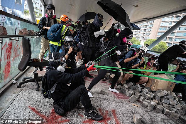 Universities in Hong Kong have this month witnessed some of the worst violent clashes between activists and police since the city's anti-government unrest began in June. Pictured, protesters use a catapult against police during in Hong Kong's City University on November 12