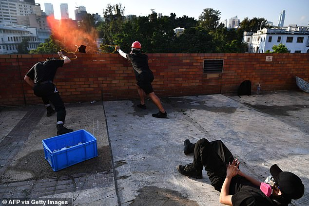 Hong Kong authorities yesterday laid down rules for students in government-run schools after the city's campuses turned into war zones due to clashes. Pictured, protesters use a catapult to fire bricks at the police from inside the Hong Kong Polytechnic University on Sunday