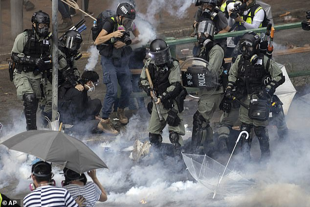 Riot police detain protesters amid clouds of tear gas at the Hong Kong Polytechnic University