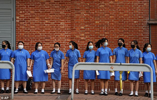 Students have been banned from forming human chains on campus. Pictured, a group of girls link hands outside St. Paul's Co-Educational College in Hong Kong on September 9
