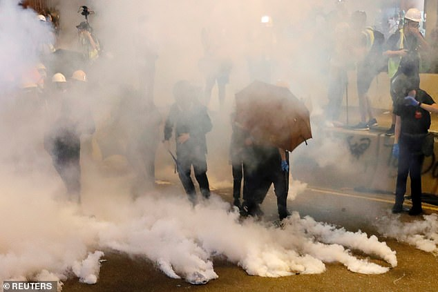 The anti-government movement was ignited in June when millions took to streets in opposition to a now-abandoned attempt to allow extraditions from Hong Kong to the mainland. Pictured, protesters react as police fire tear gas after a march to call for democratic reforms on July 21