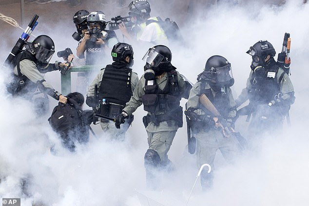 The siege at the city's Polytechnic University appeared to be nearing an end with protesters dwindling after a brutal week. Pictured, police in riot gear move through a cloud of smoke as they detain a protester at the Hong Kong Polytechnic University in Hong Kong on November 18