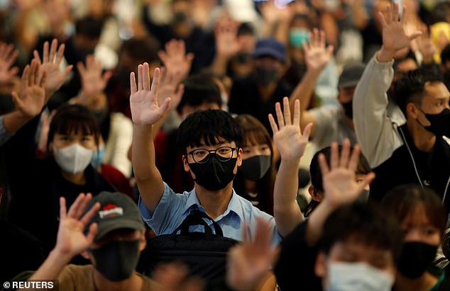 Many Hong Kong protesters have defied the mask-ban since it came into effect in October. Pictured, protesters hold up their hands during an anti-government protest at a mall yesterday