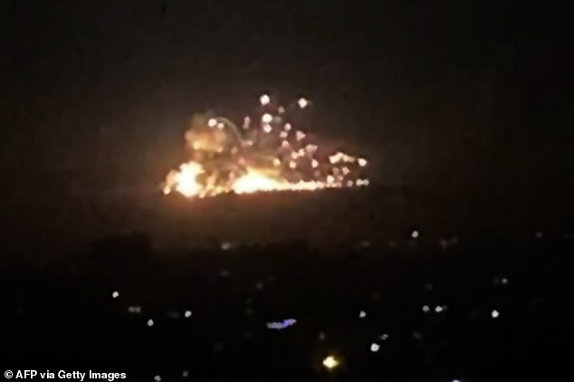 An image grab from a video posted to social media shows on smoke and fire billowing during a reported Israeli air strike on the outskirts of Damascus on Tuesday night