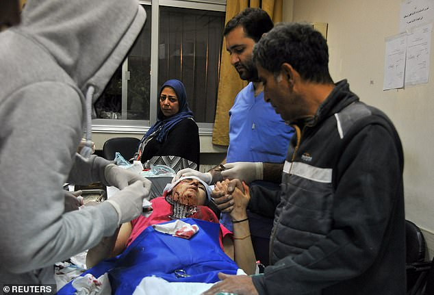 A woman injured in an explosion in Damascus last night following Israeli air strikes receives medical treatment in a photo released by Syrian state media