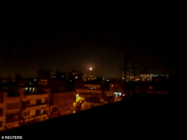 Light in the sky, believed to be a missile, is seen the city in Damascus on Tuesday night