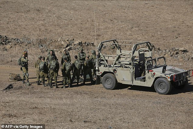Israeli soldiers are pictured near the settlement Merom Golan in the Israeli-annexed Golan Heights today following the launch of a 'wide-scale' attack on Syria by the Israeli air force