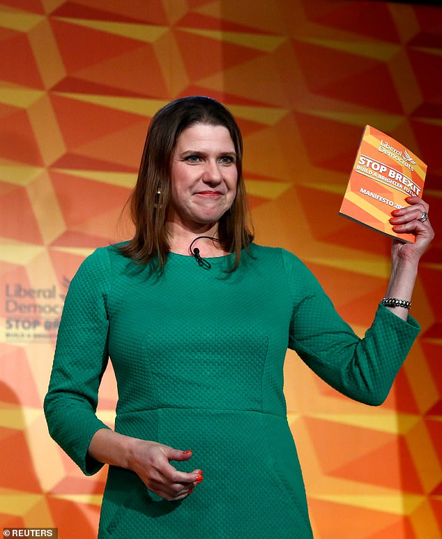 Liberal Democrat leader pictured holding up a copy of the party's manifesto on Wednesday