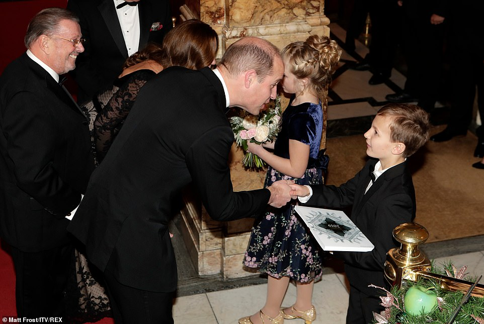 Prince William shakes the hand of eight-year-oldOliver Hinton as he's handed a copy of the programme for tonight's performance