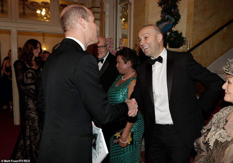 Prince William shakes hands and shares a joke with Julian Bellowes as he arrives at The Royal Variety Performance this evening