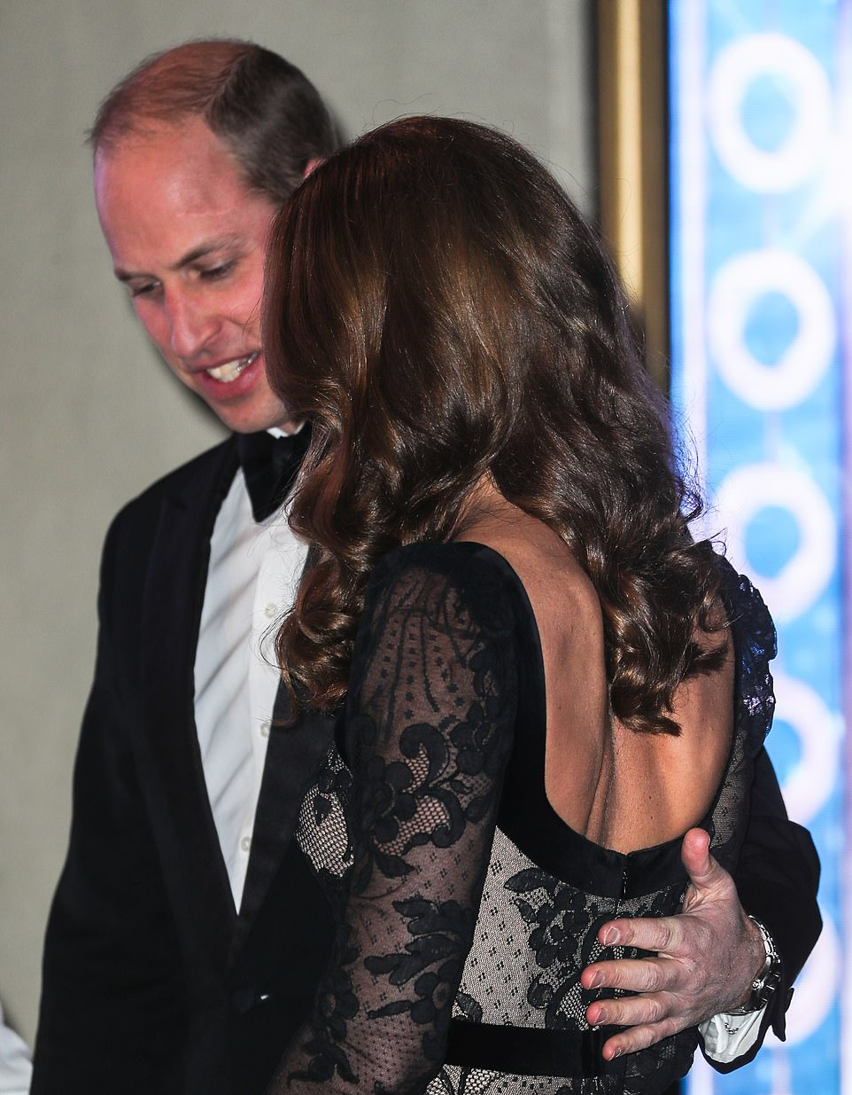 Prince William placed an affectionate hand on his wife's back as the couple entered the theatre for the performance tonight