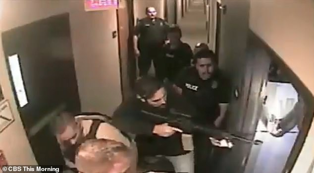 In hotel security footage armed officers surround the hotel room door. They batter down the door before a naked Webb emerges with his arms in the air