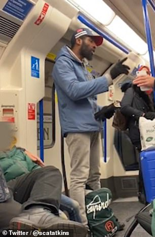 Two passengers, who appear to be father and son, are sat down wearing kippot as a man standing near the door leans over toward them as he reads aloud