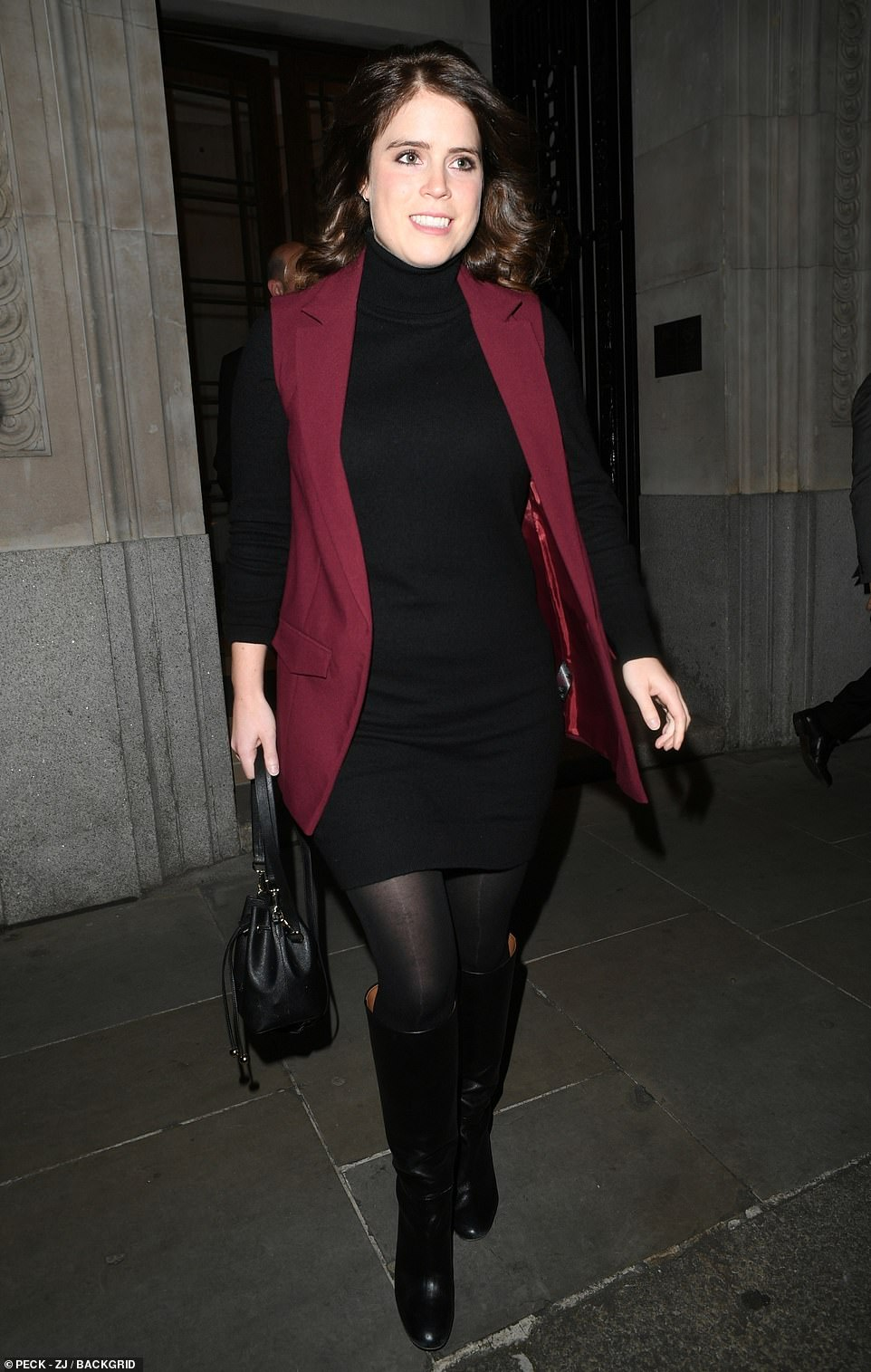 Princess Eugenie looked chic in a black long-sleeve polo neck mini-dress, as she stepped out for a charity dinner in London last night, the first time she had been spotted since her father's BBC interview