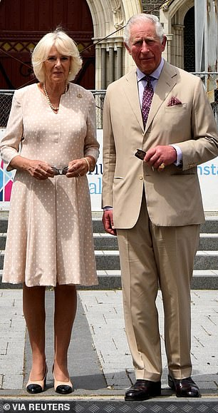 The Prince of Wales and Duchess of Cornwall are photographed in front of the damage Christchurch cathedral