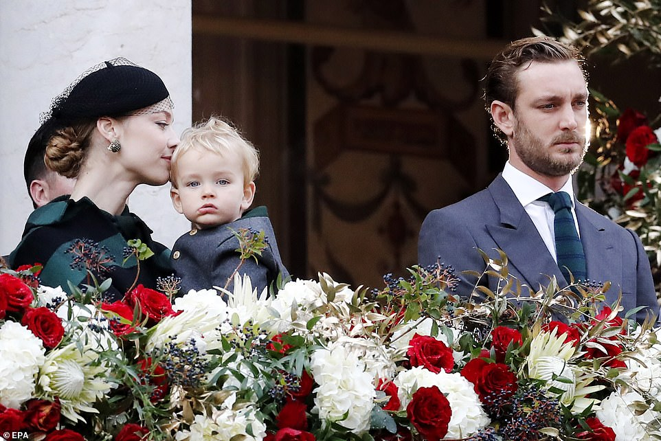 Beatrice Borromeo (Left) opted for a checked black and green cape overcoat, a stylish netted fascinator and statement earrings