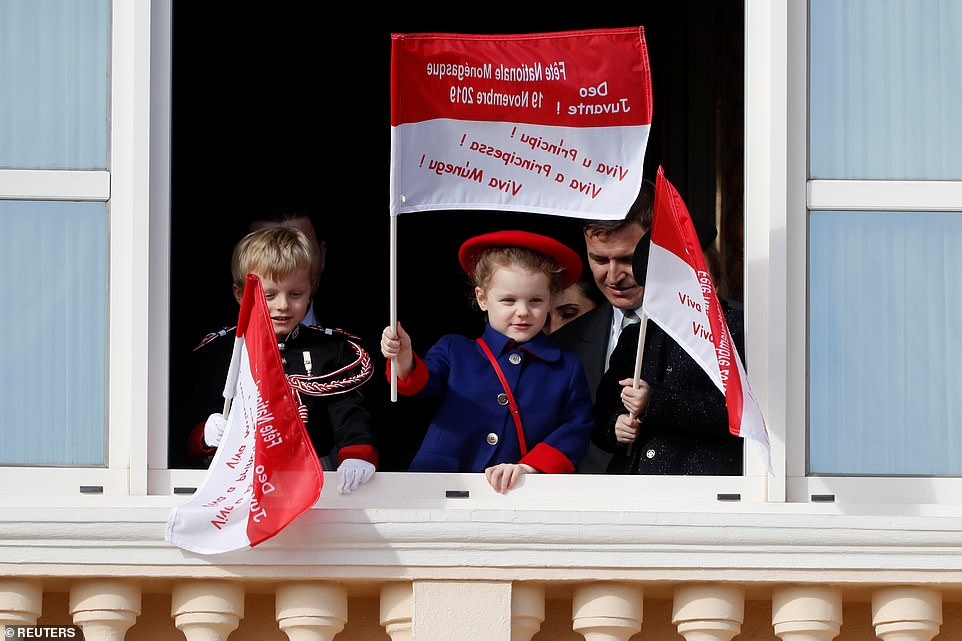 Monaco's Prince Jacques and Princess Gabriella stand on the palace balcony and hold up flags as the public watch on
