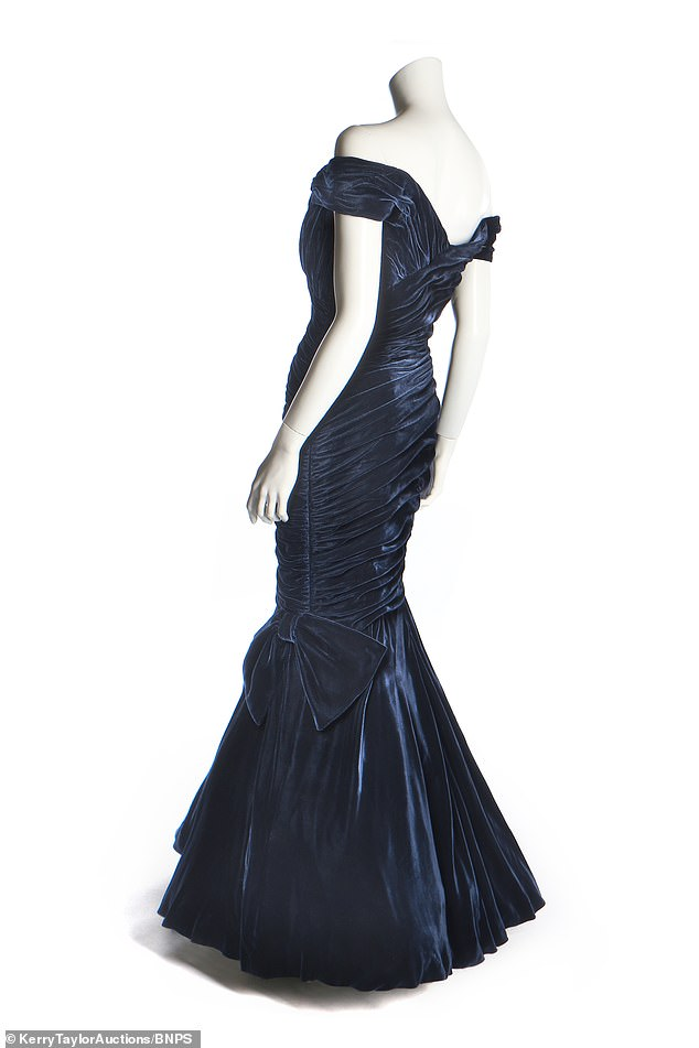 The gown has off the shoulder straps, while a diagonally swathed velvet skirt hugs the figure tightly to the knee with a bow to one side, then flares out into a broad flounce above layered tulle petticoats