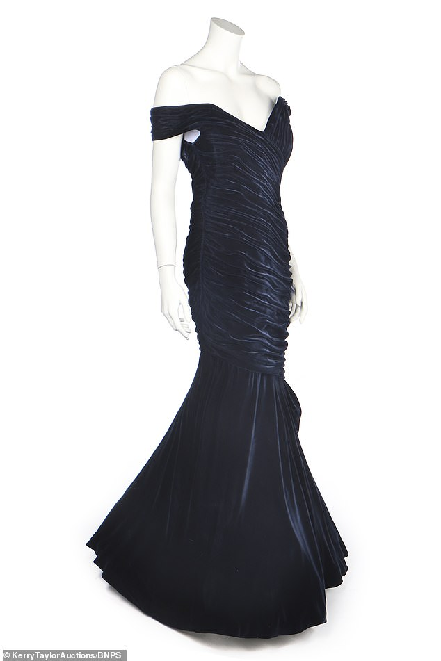 The gown has off the shoulder straps, while a diagonically swathed velvet skirt hugs the figure tightly to the knee with a bow to one side, then flares out into a broad flounce above layered tulle petticoats