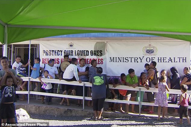 Children and parents wait in line to get vaccinated outside a health clinic in Apia, Samoa amid the outbreak that has triggered a national school closure (TVNZ via AP)